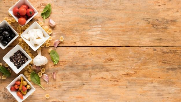 Ingredientes crus orgânicos com macarrão conchiglie na mesa marrom