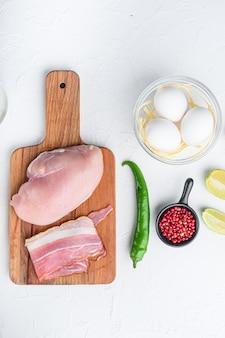 Ingredientes crus orgânicos de tacos de frango, tomates, milho, ovo, pimenta, carne de frango com limão e tortilhas sobre a vista superior do plano de fundo texturizado branco.