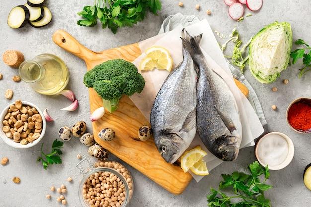 Ingredientes crus para alimentos saborosos e saudáveis. peixe fresco, legumes, ervas e legumes na vista superior do plano de fundo cinza
