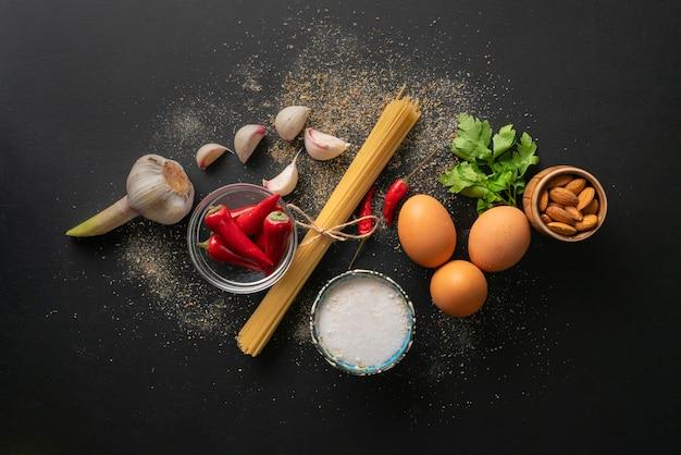 Ingredientes crus para cozinhar espaguete marinara com ovos poché plana leigos e espaços de cópia