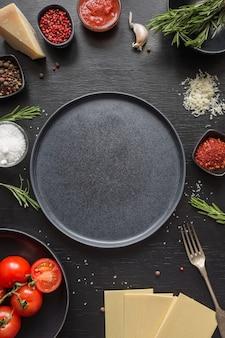 Ingredientes crus para lasanha, macarrão, legumes em preto. copie o espaço.