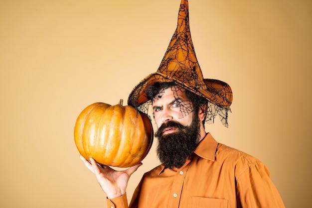Ingredientes culinários sazonais de ação de graças homem bonito de halloween com abóbora na mão barbudo hallow ...