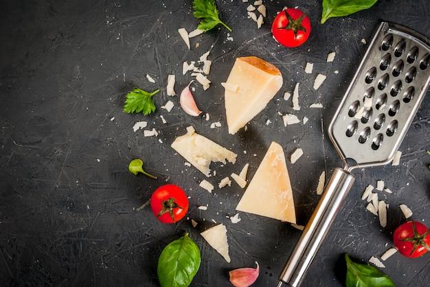 Ingredientes da cozinha italiana. parmesão ralado e um pedaço, com um ralador, folhas de manjericão, alho e tomate cereja