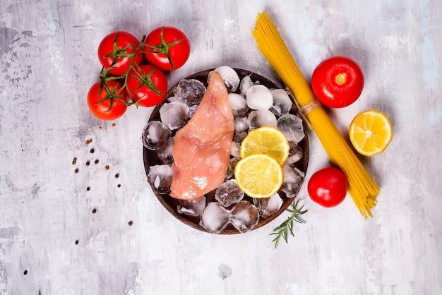 Ingredientes da massa. peitos de frango, tomate, macarrão espaguete e limão na mesa de pedra.