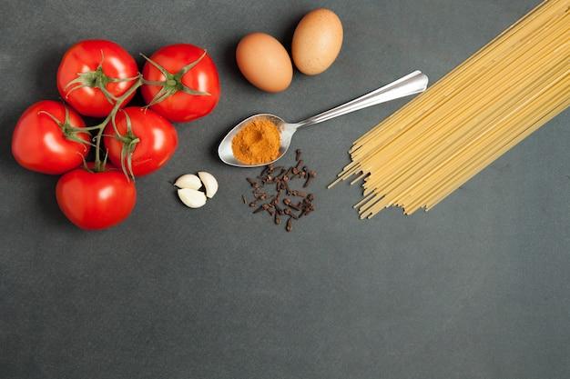 Ingredientes da massa. tomate, macarrão espaguete, alho e tomate no pano de fundo escuro grunge. orientação horizontal. vista do topo