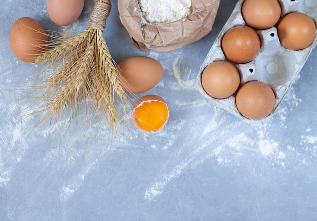 Ingredientes da padaria: ovos, espigas de trigo e saco de papel de farinha na vista superior da mesa de pedra