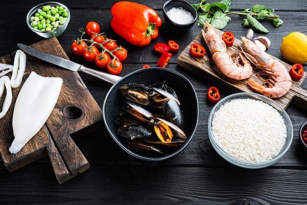 Ingredientes da paella espanhola com arroz, camarão, choco e mexilhão na mesa de madeira preta, foto de comida.