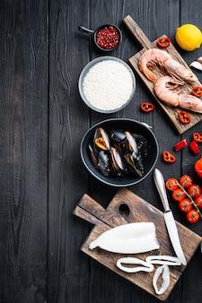 Ingredientes da paella espanhola com arroz, camarão, choco e mexilhão sobre a mesa de madeira preta, vista superior com espaço para texto, foto de comida.
