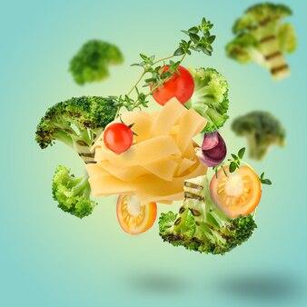 Ingredientes da pasta de fettuccine com brócolis e tomate voando no ar. copie o espaço, fundo colorido.