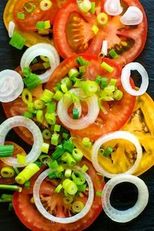 Ingredientes da salada de legumes, tomates, pepinos, cebola e verdes