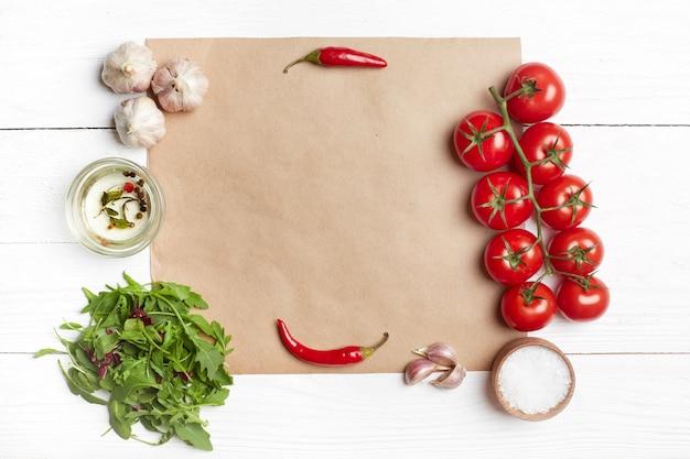 Ingredientes da salada fresca em papel pardo. vista superior, plana leigos, cópia espaço, mesa de madeira branca.