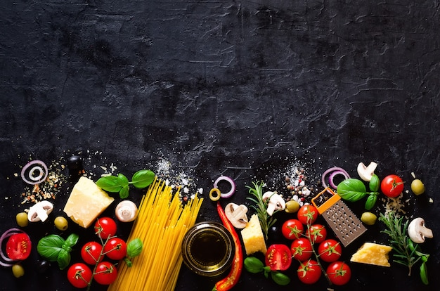 Ingredientes de alimento para a massa italiana, espaguete no fundo preto.