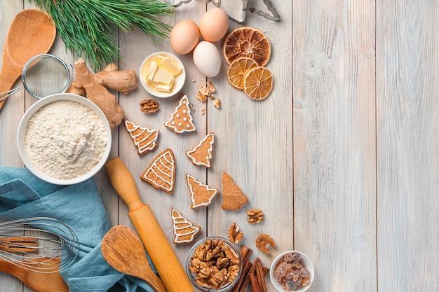 Ingredientes de biscoitos de gengibre e um galho de pinheiro em um fundo bege