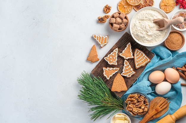 Ingredientes de biscoitos de gengibre e um galho de pinheiro em um fundo cinza