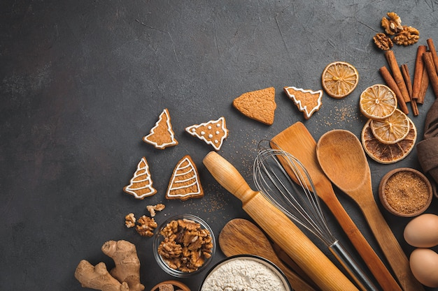 Ingredientes de biscoitos de gengibre e utensílios de cozinha em um fundo escuro vista superior do fundo de natal