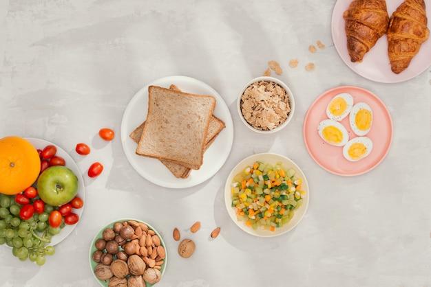 Ingredientes de café da manhã saudável em fundo preto de concreto. flocos de aveia, leite de amêndoa, nozes, frutas e bagas. Foto Premium