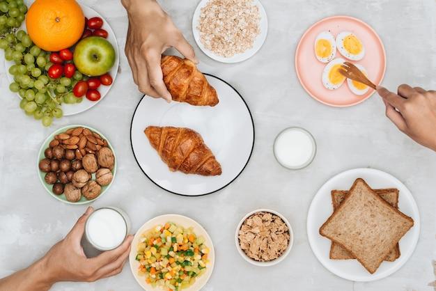 Ingredientes de café da manhã saudável em fundo preto de concreto. flocos de aveia, leite de amêndoa, nozes, frutas e bagas.