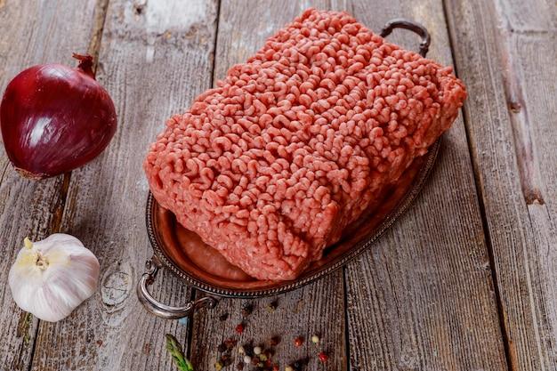 Ingredientes de carne picada crua no papel com cebola, ervas