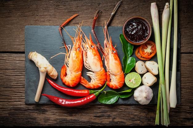 Ingredientes de comida tailandesa, preparados para cozinhar. camarão, pimentão, galangal, capim-limão, pasta de pimentão na chapa preta e mesa de madeira.