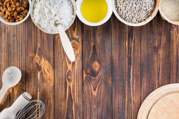 Ingredientes de cozimento na tigela sobre o fundo de madeira