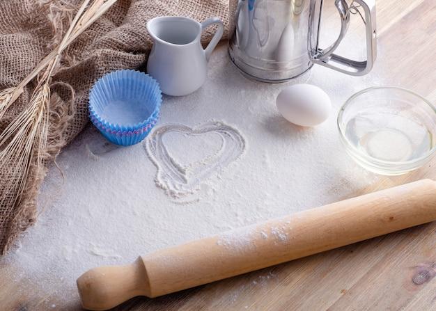Ingredientes de cozimento, ovo, farinha, óleo para assar em fundo de madeira