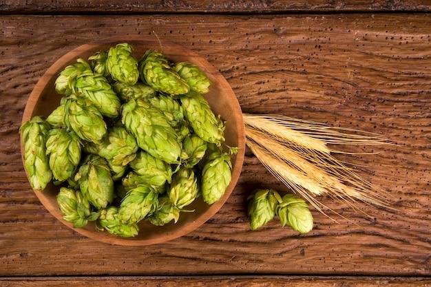 Ingredientes de fabricação de cerveja hop cones em tigela de madeira e espigas de trigo no fundo de madeira. conceito de cervejaria de cerveja.