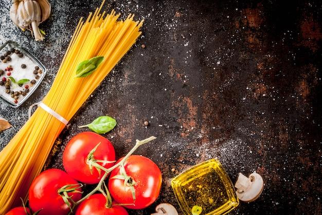 Ingredientes de fundo alimentar para cozinhar o jantar. macarrão espaguete legumes molhos e especiarias fundo escuro enferrujado