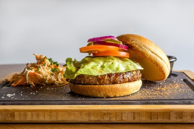 Ingredientes de hambúrguer americano em parede cinza, vista lateral