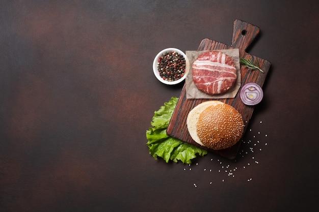 Ingredientes de hambúrguer cru costeleta, alface, pão, queijo, pepino e cebola