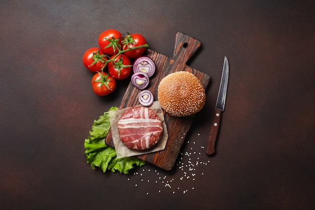 Ingredientes de hambúrguer cru costeleta, tomate, alface, pão, queijo, pepino e cebola