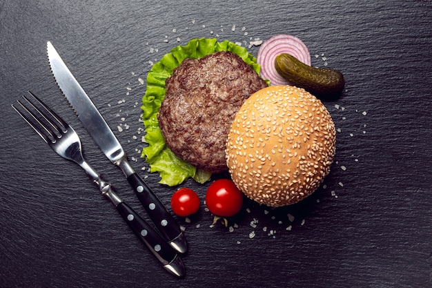 Ingredientes de hambúrguer de vista superior em fundo de ardósia