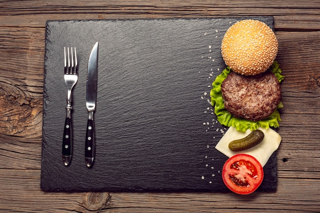 Ingredientes de hambúrguer de vista superior em uma placa de ardósia