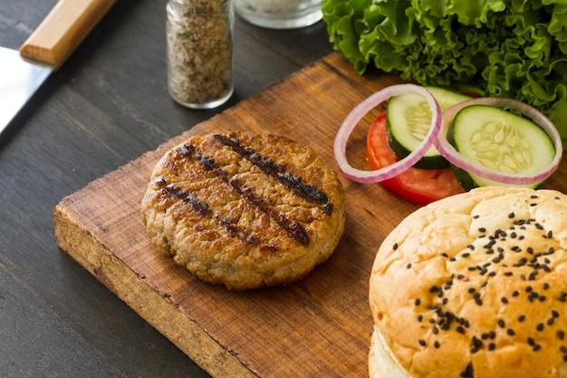 Ingredientes de hambúrguer na placa de madeira