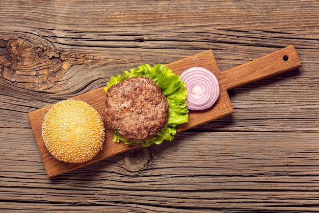 Ingredientes de hambúrgueres plana leigos em uma placa de corte