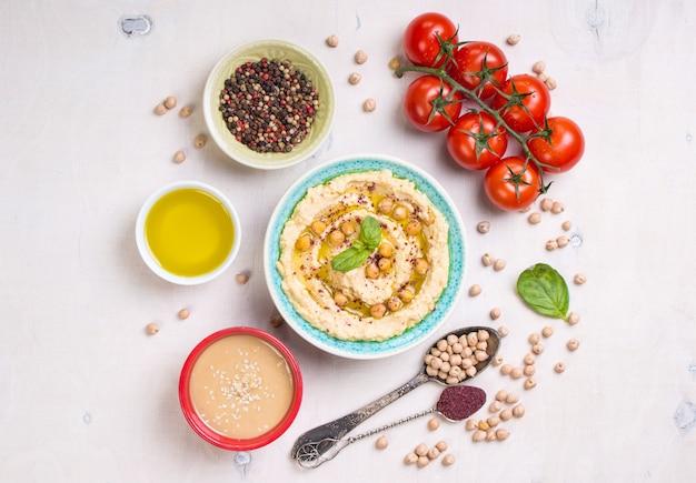 Ingredientes de homus. grão de bico, pasta de tahine, azeite, sementes de gergelim, sumagre, ervas em fundo branco de madeira rústica.