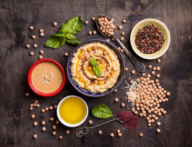 Ingredientes de homus. grão de bico, pasta de tahine, azeite, sementes de gergelim, sumagre, ervas no fundo escuro de madeira rústico.