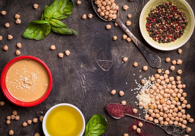 Ingredientes de homus. grão de bico, tahine, azeite, sementes de gergelim, sumagre, ervas no fundo escuro de madeira rústico. espaço para texto.