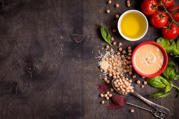 Ingredientes de homus. grão de bico, tahine, azeite, sementes de gergelim, sumagre, ervas no fundo escuro de madeira rústico.