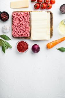 Ingredientes de lasanha crua e macarrão colocados em mesa de pedra branca vista plana