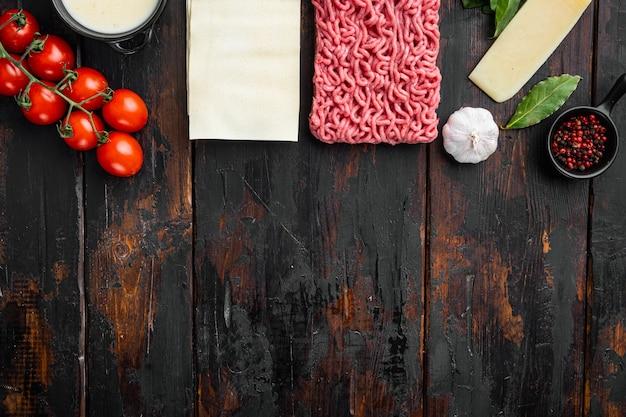 Ingredientes de lasanha crua e macarrão em uma mesa de madeira escura com vista plana e espaço de cópia