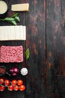 Ingredientes de lasanha de carne em uma mesa de madeira escura com vista plana e espaço de cópia