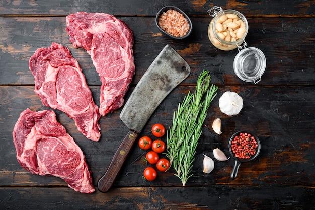 Ingredientes de lombo com feijão e faca de cutelo de açougueiro na velha mesa de madeira escura, vista de cima plana