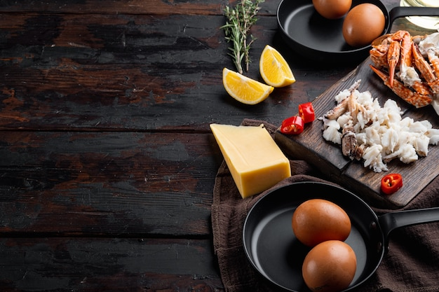 Ingredientes de omelete com pimenta, carne de caranguejo, ovo, conjunto de queijo, em fundo escuro de madeira, com copyspace e espaço para texto