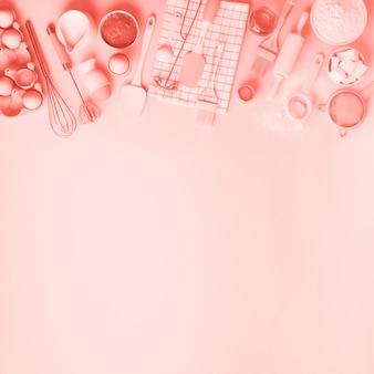 Ingredientes de padaria sobre fundo de cor coral - manteiga, açúcar, farinha, ovos, óleo, colher, rolo, escova, bata, toalha. quadro de cozimento, conceito de cozinha. vista superior, copie o espaço. configuração plana