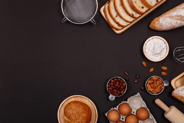 Ingredientes de pães caseiros, farinha, nozes amêndoas, avelãs, ovos em fundo escuro.
