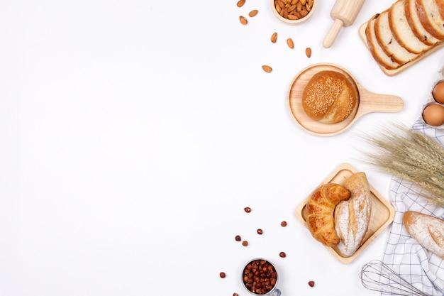 Ingredientes de pães caseiros, farinha, nozes amêndoas, avelãs, ovos no fundo branco.