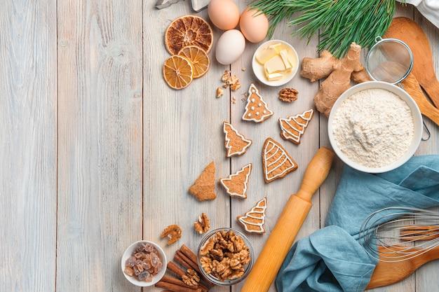 Ingredientes de panificação, biscoitos de gengibre e um galho de pinheiro em um fundo bege. fundo de natal