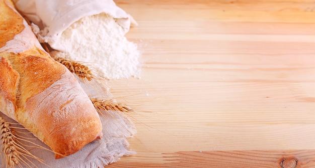 Ingredientes de panificação: farinha e ouvidos sobre um fundo claro de madeira