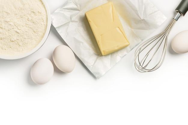 Ingredientes de panificação isolados no fundo branco. composição plana com farinha, manteiga, ovos e um batedor.