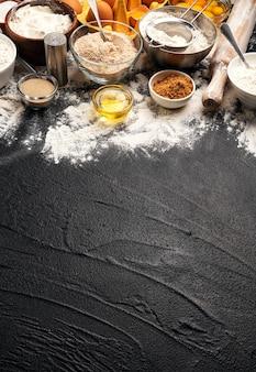 Ingredientes de panificação para massa em fundo preto